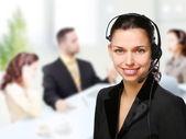 Mulher de operador de suporte ao cliente sorrindo para um escritório — Foto Stock