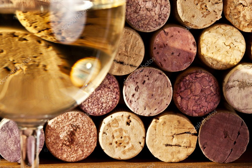 Image of wine corks through a glass of white wine.  Stock Photo #5005127