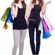 Stock Photo: Image of two girls with their purchases. Isolated on white backg
