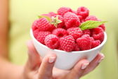 Crockery with raspberries in woman hand. — Stock Photo
