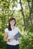Chica exitosa en el bosque con un libro — Foto de Stock