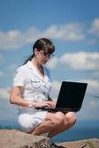 Una mujer exitosa con un portátil sentado en una piedra — Foto de Stock
