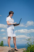Business woman with laptop standing on a rock — Stock Photo