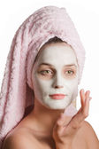 Beautiful girl in a rejuvenating mask with towel — Stock Photo