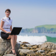 Beautiful girl sits on a rocky shore — Stock Photo