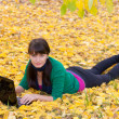 Beautiful girl with a laptop in a autumn foliage — Stock Photo