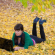Beautiful young girl with a yellow autumn foliage — Stock Photo