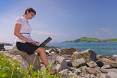 Beautiful young sexy business woman with laptop at the sea — Stock Photo