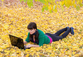 Girl with a laptop in a yellow autumn foliage — Stock Photo