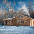 Small wooden house in a snowy forest — Stock Photo #4385395
