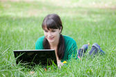 Beautiful girl with a laptop in the grass — Stock Photo