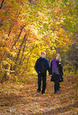 Active beautiful boy and girl in autumn wood — Stock Photo
