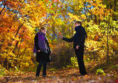 Beautiful boy and girl in autumn wood — Stock Photo