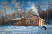 Small wooden house in a snowy forest — Stock Photo