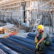 Construction worker resting on steel bars - Stok fotoğraf
