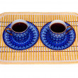 Two elegant porcelain cups with coffee at a yellow bamboo mat isolated — Stock Photo #4010667