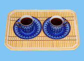 Two elegant porcelain cups with coffee at a yellow bamboo mat — Stock Photo