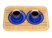 Two elegant porcelain cups with coffee at a yellow bamboo mat isolated — Stock Photo
