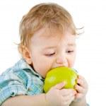 Beautiful baby boy eats green apple. — Stock Photo #4810965