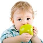 Beautiful baby boy eats green apple. — Stock Photo #4810990
