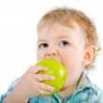 Beautiful baby boy eats green apple. — Stock Photo #4811011