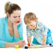 Royalty-Free Stock Photo: Young mum draws with the son paints