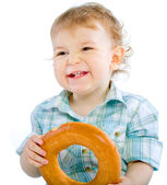 Little baby boy holding a bagel — Stock Photo