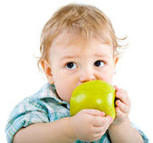 Beautiful baby boy eats green apple. — Stock Photo