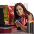 Stock Photo: Young pretty women is buying in internet