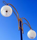 Dirty broken street light against the blue sky — Stock Photo