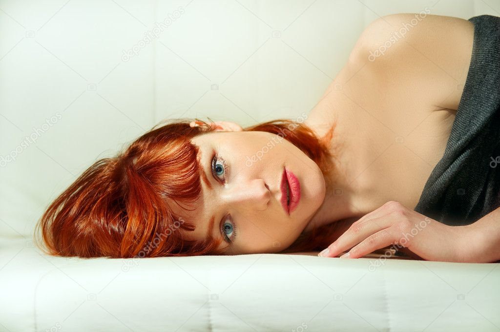 Portrait of the young girl with red hair in a prone position. — Stock Photo #4778399