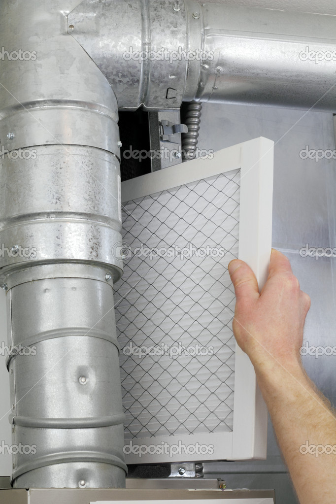 A man's arm and hand seen replacing disposable air filter in home central air furnace.  Foto Stock #5134891