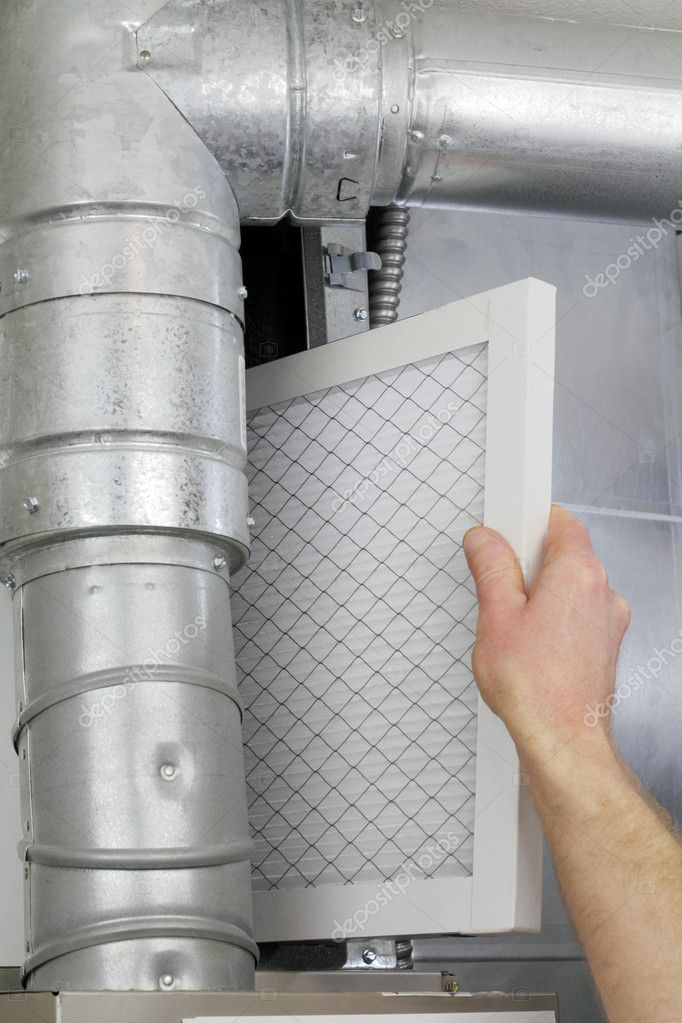 A man's arm and hand seen replacing disposable air filter in home central air furnace.  Stockfoto #5134891
