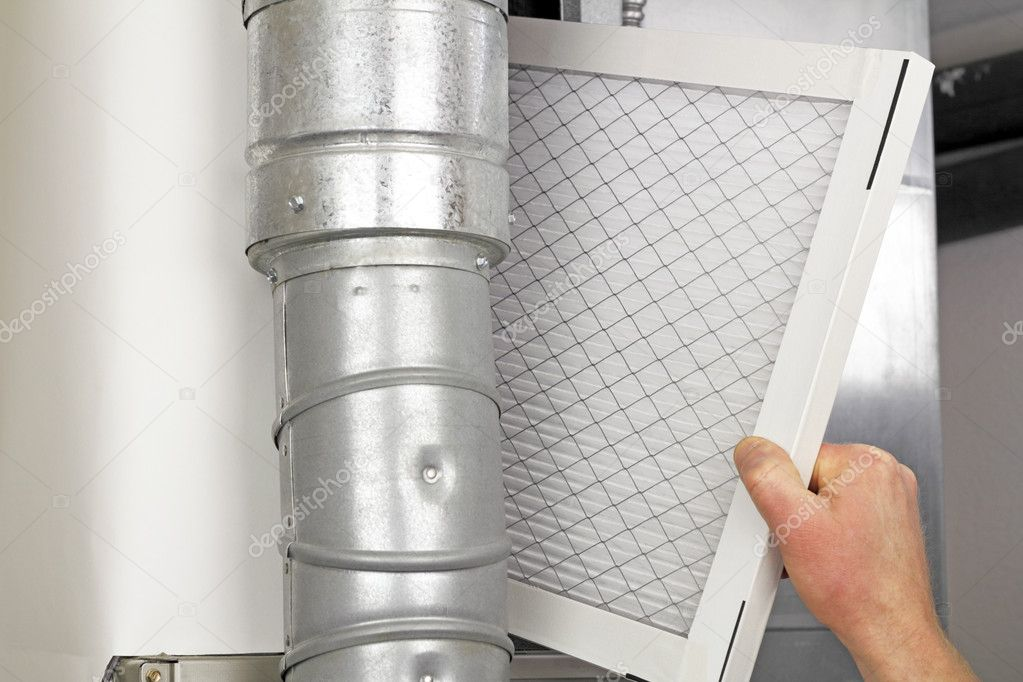 Male arm and hand replacing disposable air filter in residential air furnace. — Stock Photo #5134943