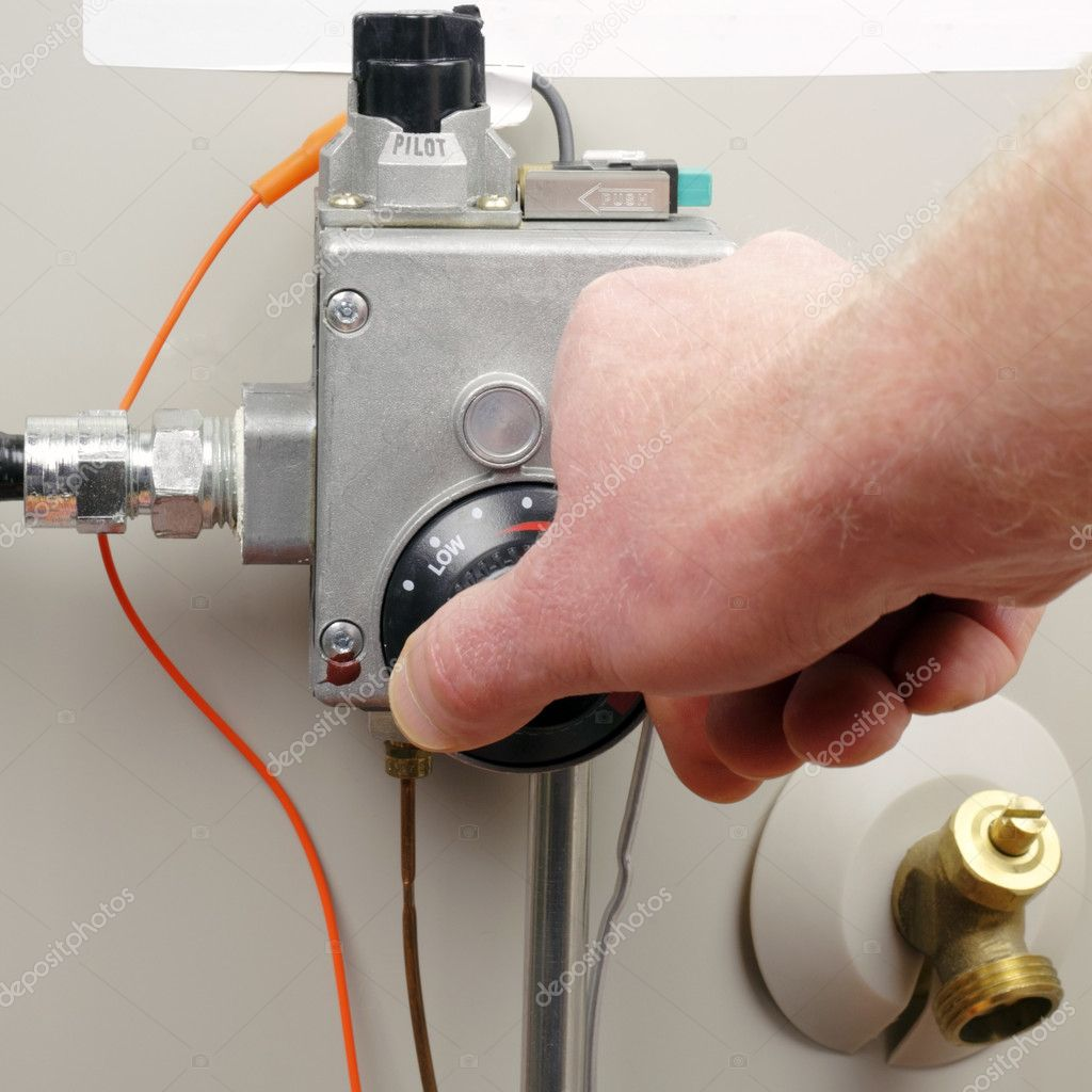 Hand of a man turning down household gas water heater temperature. — Stock Photo #5184206