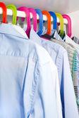 Kläderna på den färgade klädhängare i garderoben — Stockfoto