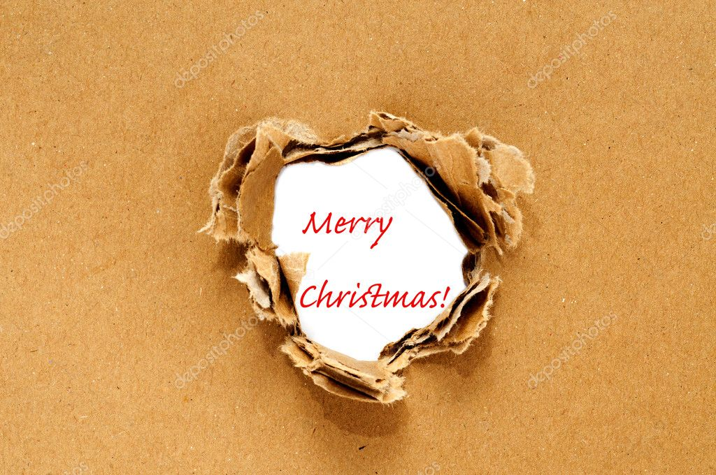 Merry Christmas written on a hole on a brown cardboard background — Stock Photo #4220078