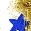 A blue christmas star and golden tinsel on a white background - Stock Photo