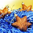 Some golden christmas stars on blue tinsel — Stock Photo