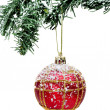 A red and golden christmas ball hanging on a snowy christmas tree - Stockfoto