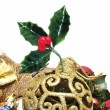 A golden christmas ball and other christmas ornaments on a white background - Stockfoto