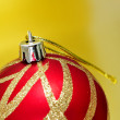 Red and golden christmas ball on a golden background - Stockfoto