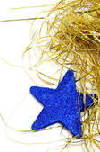 A blue christmas star and golden tinsel on a white background — Stock Photo