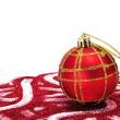 Red and golden christmas ball with red glitter on a white background - Stockfoto