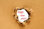 Happy new year written on a hole on a brown cardboard background — Stock Photo