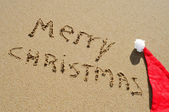 Merry christmas written in the sand and a santa had — Stock Photo