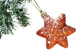 A golden christmas star hanging on a christmas tree on a white background — Stock fotografie