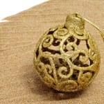 A golden christmas ball on the sand — Stock Photo