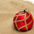 A red and golden christmas ball on the sand - Stock Photo