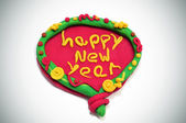 Happy new year written in a design made with modelling clay — Photo